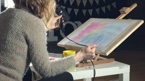 Краска взрослых женщин с покрашенными красками акварели и сушит с феном для волос в художественном училище