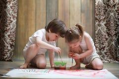 Краска маленьких детей на большом листе бумаги стоковая фотография rf