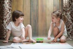 Краска маленьких детей на большом листе бумаги стоковая фотография