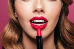 Краска молодой дамы ее губы при красная изолированная губная помада Стоковые Изображения RF