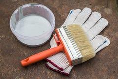 Краска, перчатки, щетка на ржавой плите Стоковое Фото