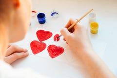 Краска руки ` s женщины красит сердце стоковые фото