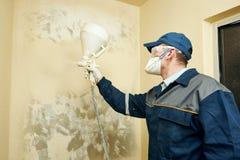 Краска художника распыляя на стене внутри помещения Стоковое Изображение
