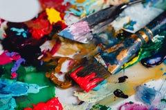 Краска щетки искусства смешанная на палитре Инструменты художника к, запятнанные в чернилах после работы стоковые изображения