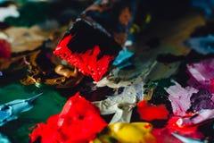Краска щетки искусства смешанная на палитре Инструменты художника к, запятнанные в чернилах после работы стоковая фотография rf