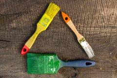 Краска 3 щеток на деревянной предпосылке сверху Стоковые Изображения RF