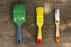 Краска 3 щеток на деревянной предпосылке сверху Стоковые Изображения