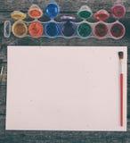 Краски акварели установили с щетками и бумажным листом Стоковая Фотография