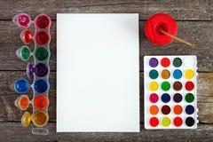 Краски акварели установили с щетками и бумажным листом Стоковая Фотография RF