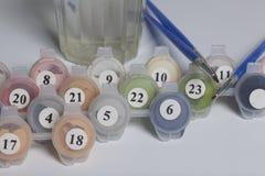 Краски для рисовать номерами Несколько контейнеров с краской открыты Tassels, лист бумаги рядом стоковые фотографии rf