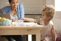 Краски девушки на кухонном столе как мать работают на компьтер-книжке Стоковая Фотография