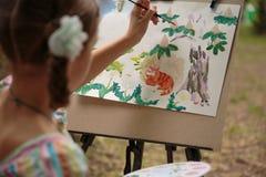 Краски девушки на мольберте в уроке чертежа стоковое изображение rf