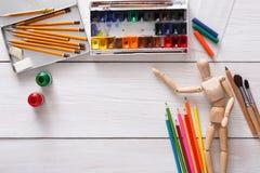 Краски и деревянный человек с щетками, объект художника Стоковая Фотография RF