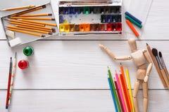 Краски и деревянный человек с щетками, объект художника Стоковые Изображения RF