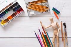 Краски и деревянный человек с щетками, объект художника Стоковое Изображение