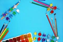 Краски и щетки акварели на голубой предпосылке Стоковое фото RF
