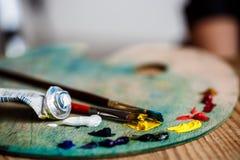 Краски и щетки масла на палитре над деревянной предпосылкой Стоковое фото RF