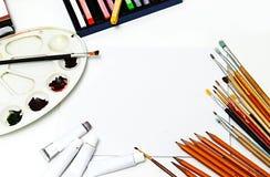 Краски и щетки на белой предпосылке холста Насмешка кисти искусства и белых холста вверх Стоковые Фотографии RF