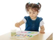 Краски маленькой девочки с акварелями на таблице Стоковая Фотография RF