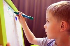 Краски мальчика на мольберте Стоковая Фотография