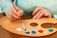 Краски художника смешивая на палитре Стоковое Изображение RF