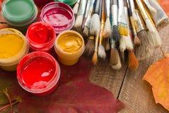 Краски, щетки, листья осени на деревянной предпосылке Стоковые Изображения RF