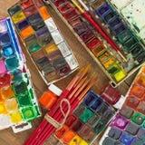 Краски, щетки и палитра акварели на деревянной предпосылке Стоковая Фотография RF