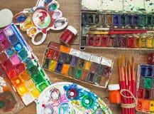 Краски, щетки и палитра акварели на деревянной предпосылке Стоковые Фото