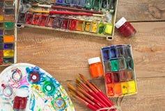Краски, щетки и палитра акварели на деревянной предпосылке Стоковые Изображения RF