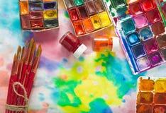 Краски, щетки и палитра акварели на красочной предпосылке Стоковая Фотография
