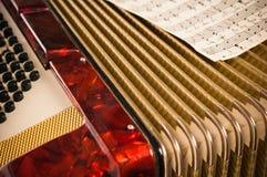 Красная аккордеоня и ноты стоковое фото