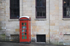 Красная английская традиционная общественная телефонная будка на улице стоковое фото rf