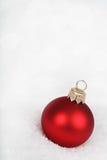 Красная безделушка на снеге стоковое изображение