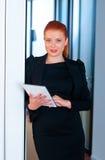 Красная бизнес-леди волос с таблеткой в офисе Стоковые Изображения RF