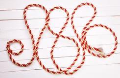 Красная веревочка на белом деревянном столе предпосылки Стоковые Фото
