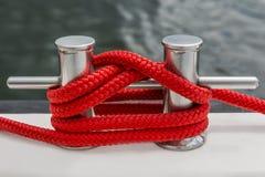 Красная веревочка прикрепляет на коле яхты стоковое фото