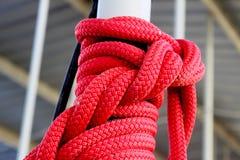 Красная веревочка связанная в сложном узле вокруг поляка на доке Стоковое Изображение RF
