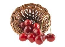 Красная вишня в плетеной корзине изолированной на белизне Стоковая Фотография RF