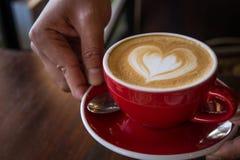 Красная влюбленность кофе чашки, темнота кофе в деревянной темной таблице Стоковое фото RF