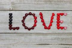 Красная ВЛЮБЛЕННОСТЬ произношения по буквам сердец конфеты Стоковые Фото