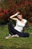 Красная дама волос обтирая пот от лба после тренировки в парке стоковое изображение