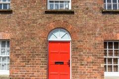 Красная дверь на доме красного кирпича стоковые изображения rf