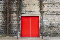 Красная дверь на кирпичном здании стоковая фотография rf