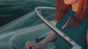 Красная девушка волос в моторной лодке кормила платья бирюзы за валами 2 захода солнца лета сосенки стоящими зрелищность акции видеоматериалы