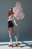 Красная девушка волос на роликах есть мороженое и держа воздушные шары стоковые изображения rf