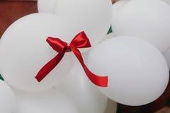 Красная лента на пуке белых декоративных baloons воздуха, воздушных шаров мы Стоковые Изображения