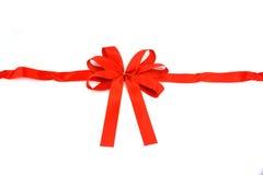 Красная лента с смычком на белой предпосылке Стоковая Фотография