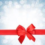 Красная лента с смычком над предпосылкой снега рождества Стоковая Фотография