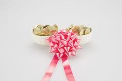 Красная лента с стогом золотых монеток в керамической чашке Стоковое Изображение