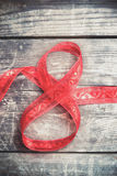 Красная лента торжества подарка в форме 8 чисел над деревенским деревянным ба Стоковое Изображение RF
